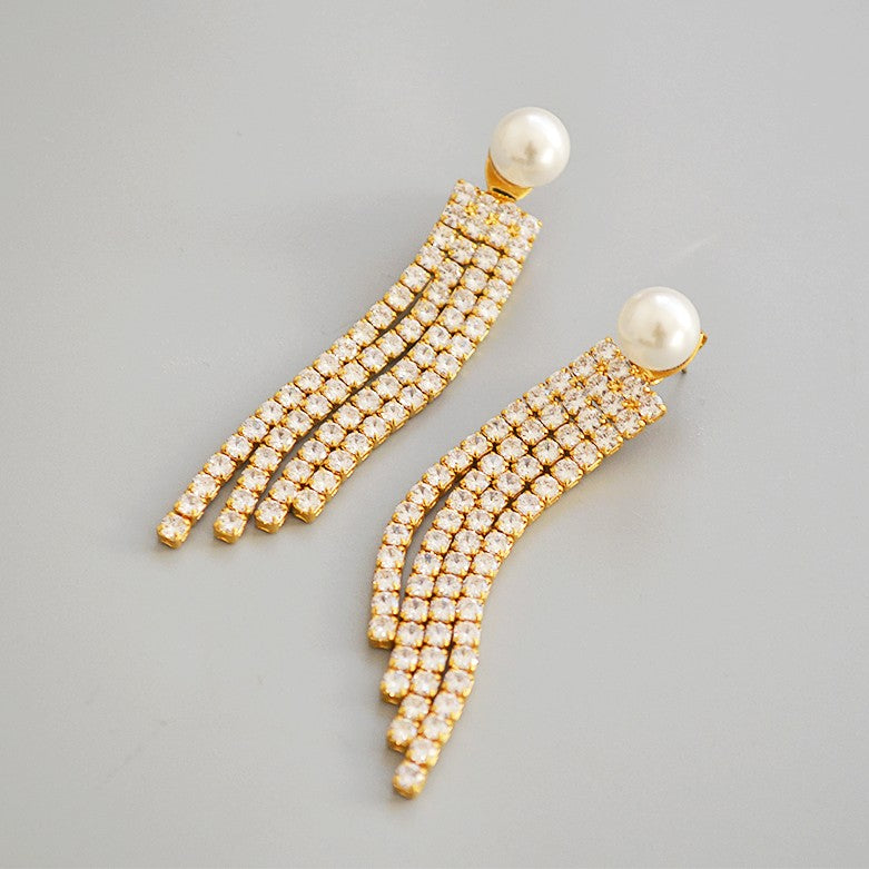 golden tassel earrings embellished with crystals and pearl globes displayed on grey background