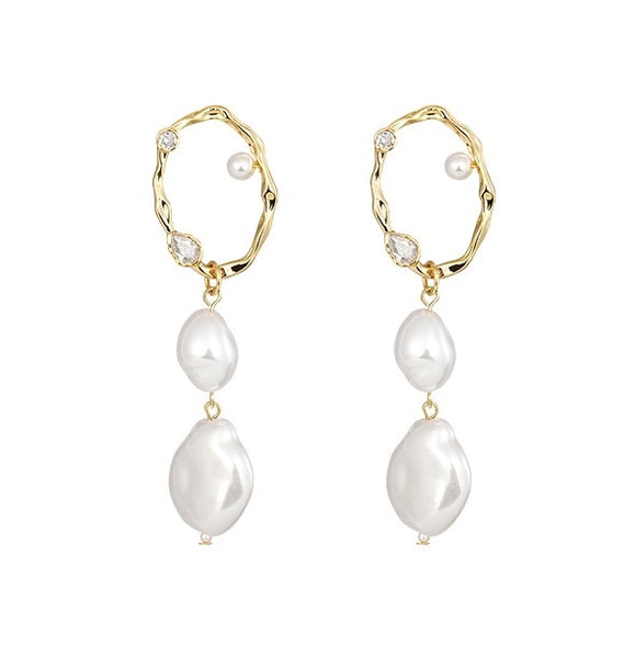 Double baroque pearl drop earrings suspend from a golden hoop displayed on light background