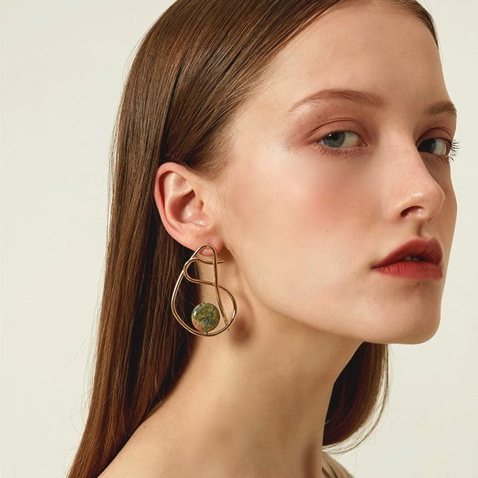 twisted golden hoop earring with a green natural bead on model