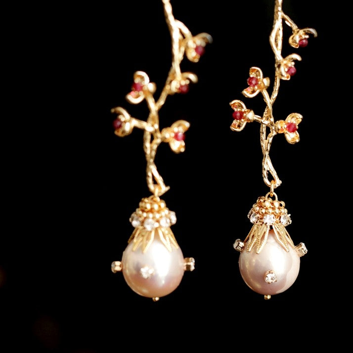 golden pearl drop earrings featuring flower branch motifs displayed on black background