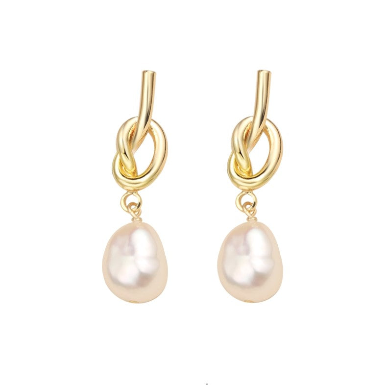 golden tie knot earrings with baroque pearl drops displayed on white background
