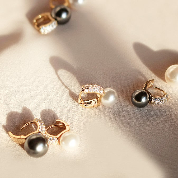 black and white freshwater pearl drops suspended from micro golden hoops displayed on beige background