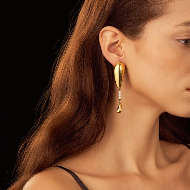 golden drop earring featuring crystal pear globes on model