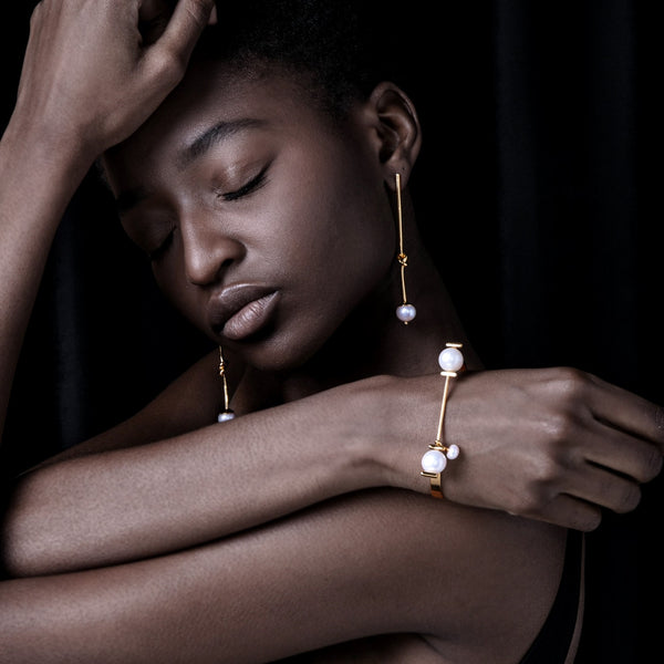 gold bracelet and earrings feature freshwater pearl globes on model