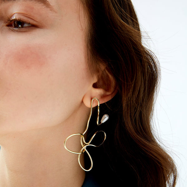 Avant-garde gold twisted earring accented with tear-drop pearl on model
