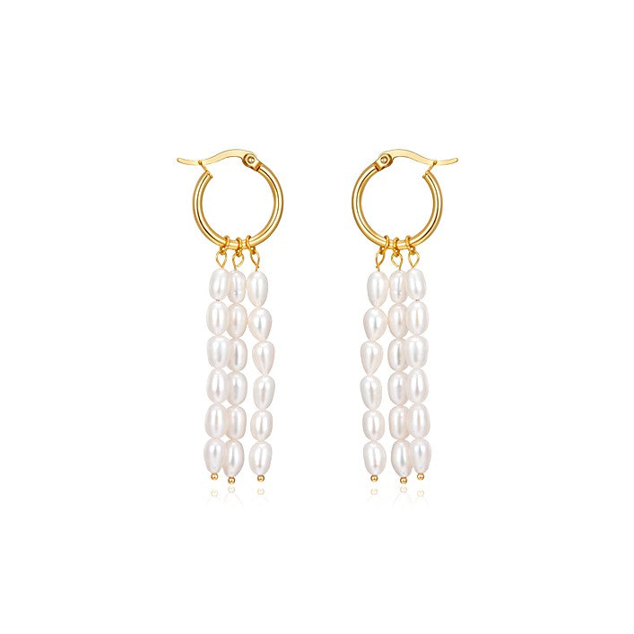 chandelier pearl earrings suspended from a golden hoop displayed on white background