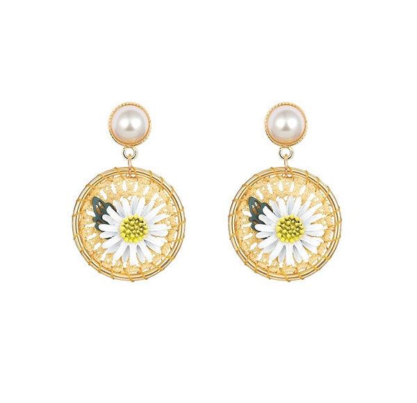 round daisy flower drop earrings featuring white lily flower in the middle suspend from white pearl studs displayed on white background