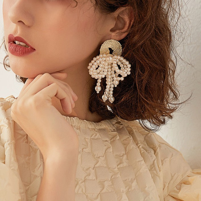 pearl bow drop earring suspended from a golden dial on model
