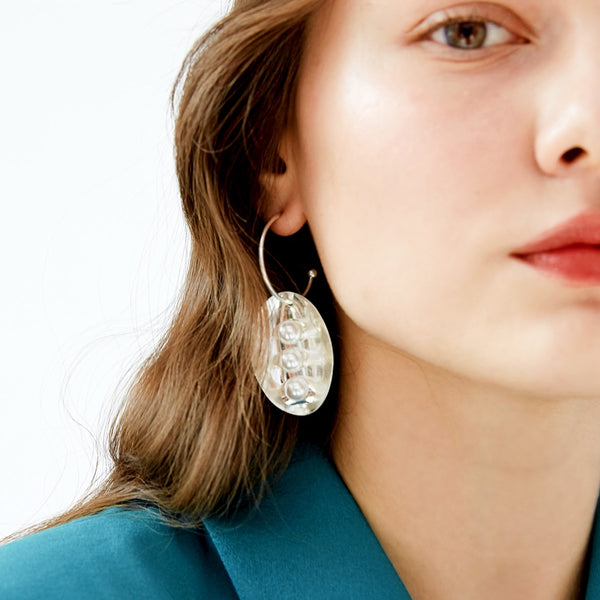 peapod inspired oval-drop earring on model
