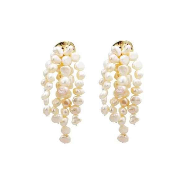 freshwater pearl chandelier earrings suspend from golden disks on white background