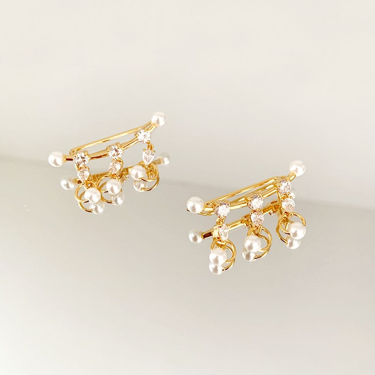 triple crystal and pearl bar earrings displayed on light grey background