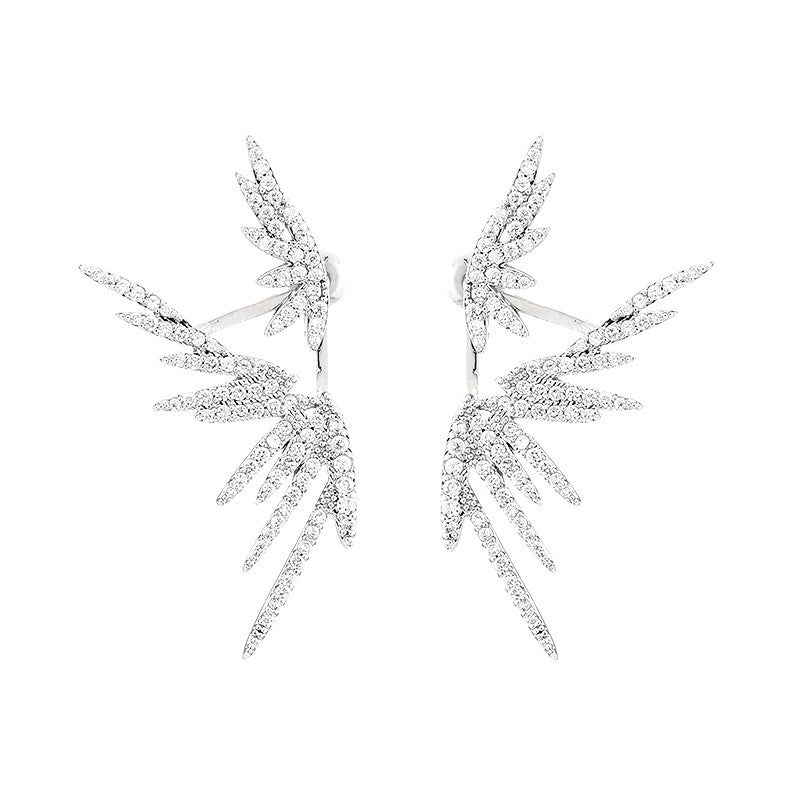 silver dual wing earrings on white background