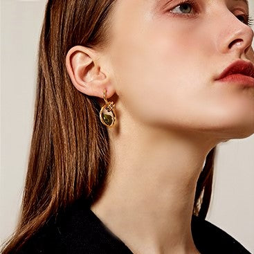 golden micro hoop earring with gemstone in the center on model