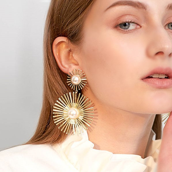 golden round drop earring in a sun dial shape on model