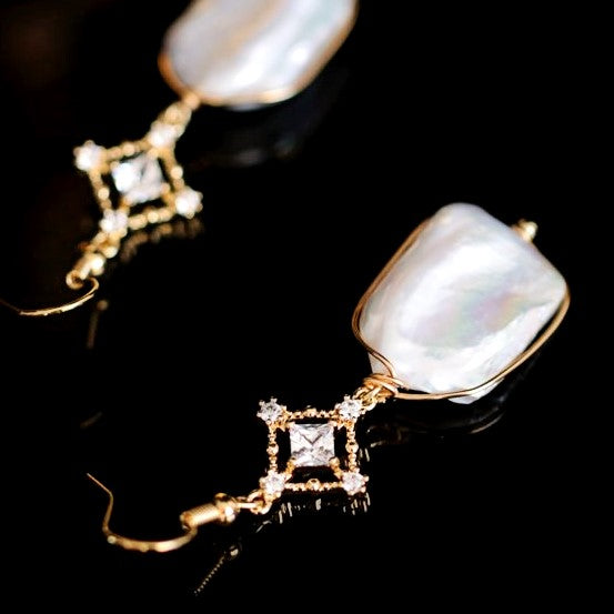 Art deco inspired rectangular baroque drop earrings with crystal cross motifs displayed against black background