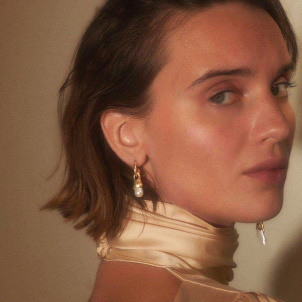 long and short golden bar pearl drop earrings on model in silk dress