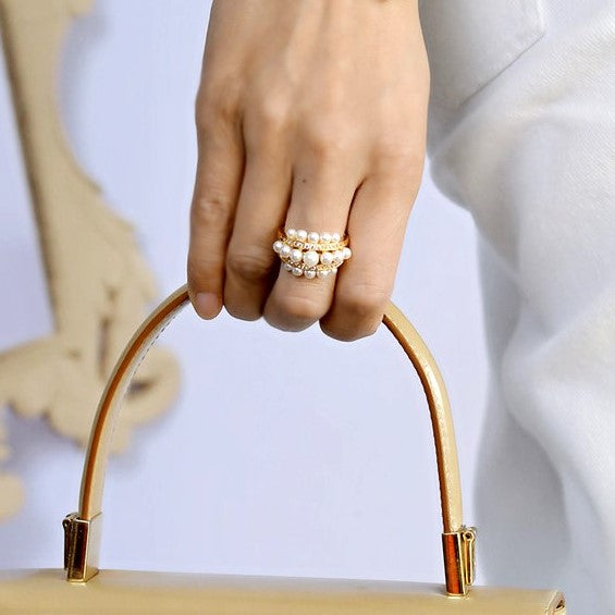 three-tier golden ring with pearls on model hand
