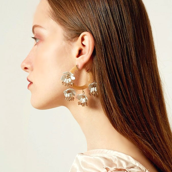 honey colored acrylic hoop earrings with four white flower drops on model