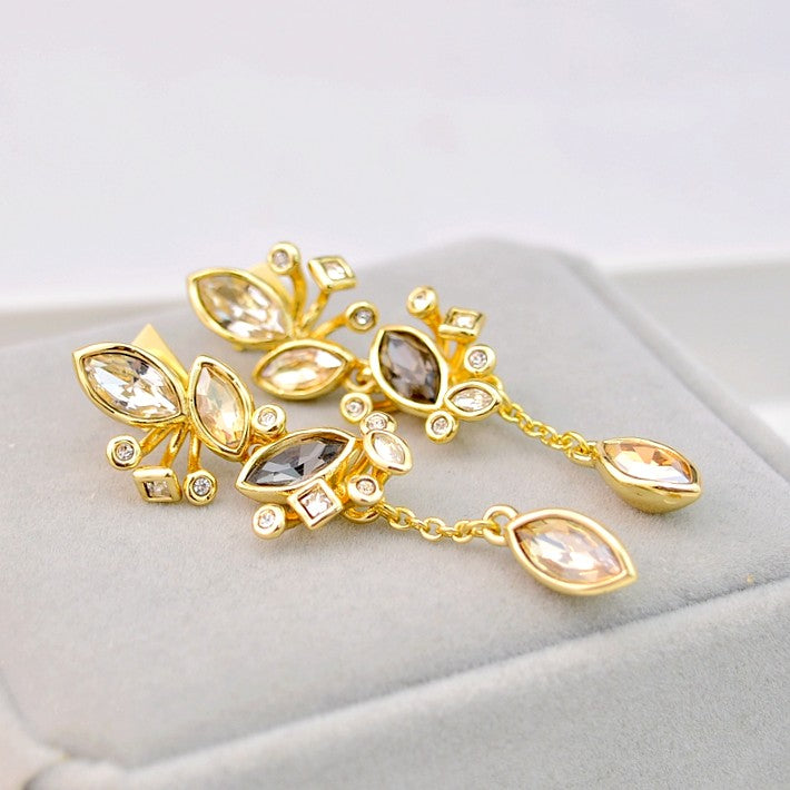 golden earrings featuring warm gold-tone with ornate clusters of colored crystals displayed on grey background