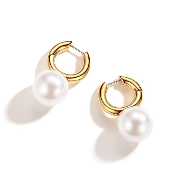 golden hoop earrings feature large pearl globe drop on white background