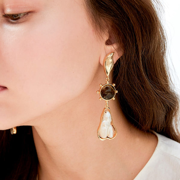 large baroque pearl drop earring feature gold accents and brown mother of pearl embellishment on model