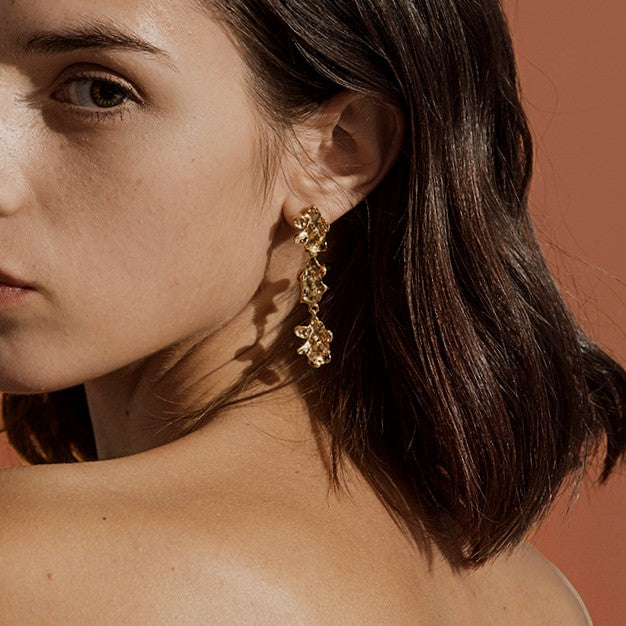 long golden drop earring featuring a string of three nuggets on model