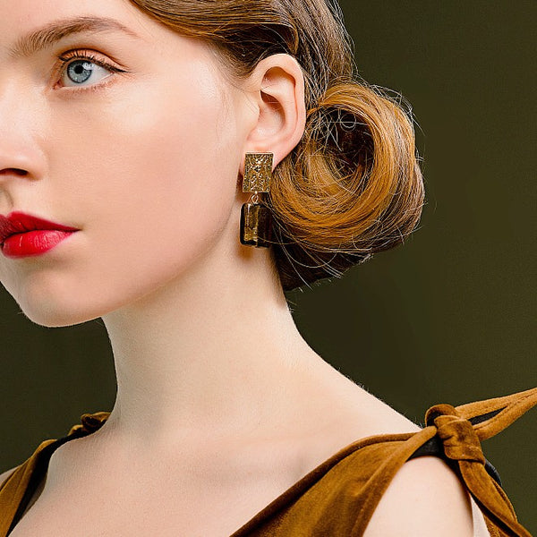 gold and brown square drop earring on model
