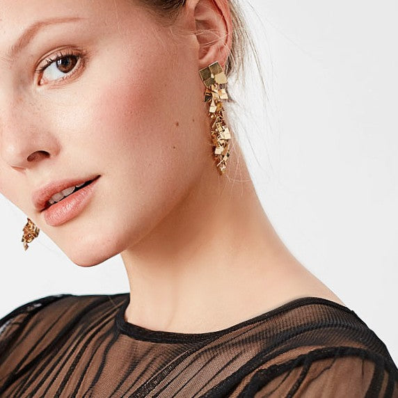 golden drop earrings on model