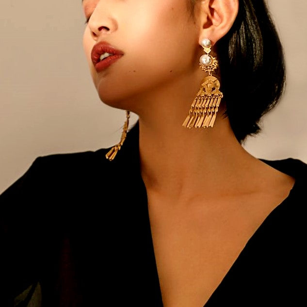 dramatic gold drop earrings decorated with pearl globes on model