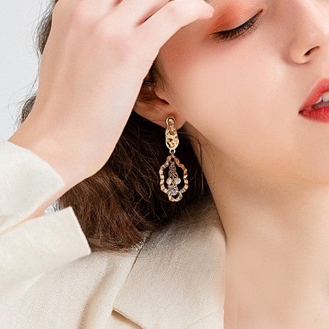 asymmetric golden drop feature sparkling crystals on model