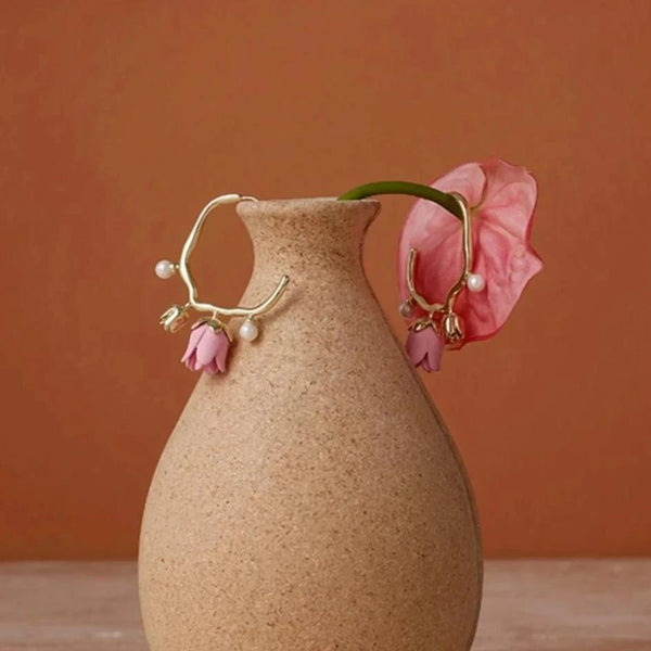 Golden hoop earrings with flower and pearl decor displayed on brown vase
