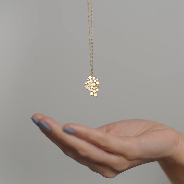 sculpted gold necklace displayed on grey background on top of a hand