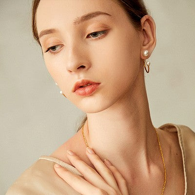 golden open hoop earrings featuring pearl globes on each end on model