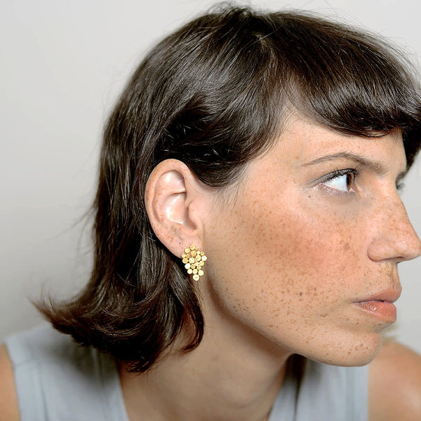 sculpted gold stud earring on model