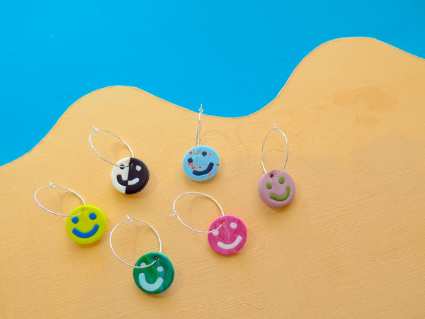 Small hoop earrings with smiley happy faces by Baked by Lou with 20% going to charity