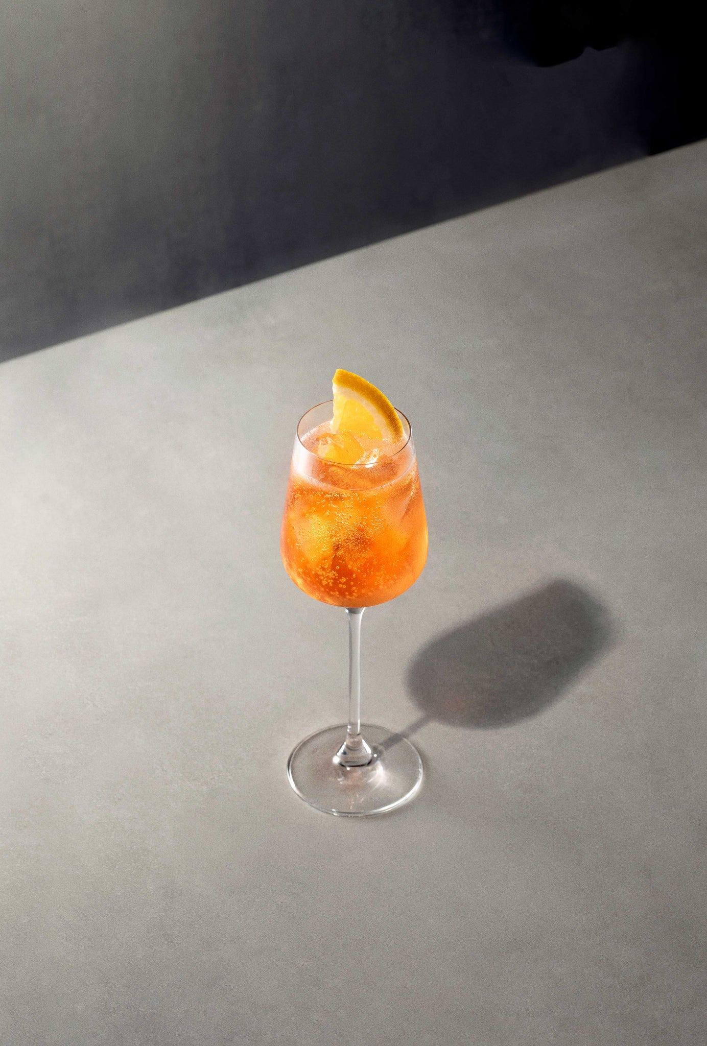 Black Lines Aperol Spritz Cocktail single serve in clear wine glass with cubed ice and garnished with an orange slice