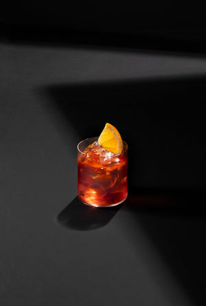 Black Lines Negroni cocktail in a clear rocks glass with cubed ice and garnished with an orange slice