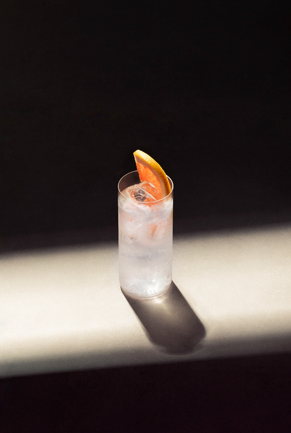 Black Lines Paloma Cocktail single serve in highball glass with cubed ice and garnished with a pink grapefruit slice