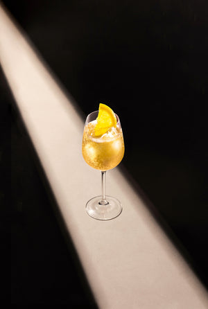 Black Lines Pear & White Tea Fizz cocktail single serve in a clear wine glass with cubed ice and garnished with a lemon slice.