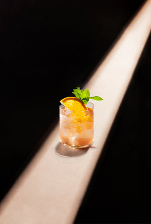 Black Lines Rum Punch Cocktail single serve in a clear rocks glass with cubed ice and garnished with an orange slice and mint sprig