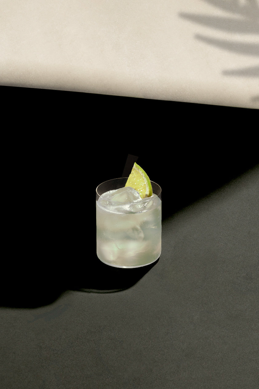 Black Lines Tommy's Margarita cocktail single serve in a clear rocks glass with cubed ice and garnished with a lime slice