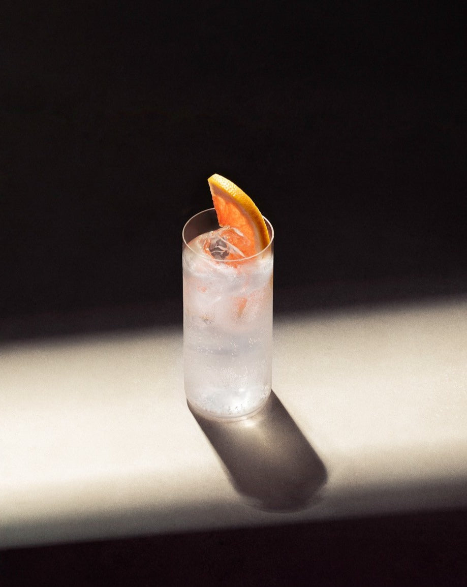 Paloma cocktail in glass with ice and garnished with a slice of pink grapefruit.