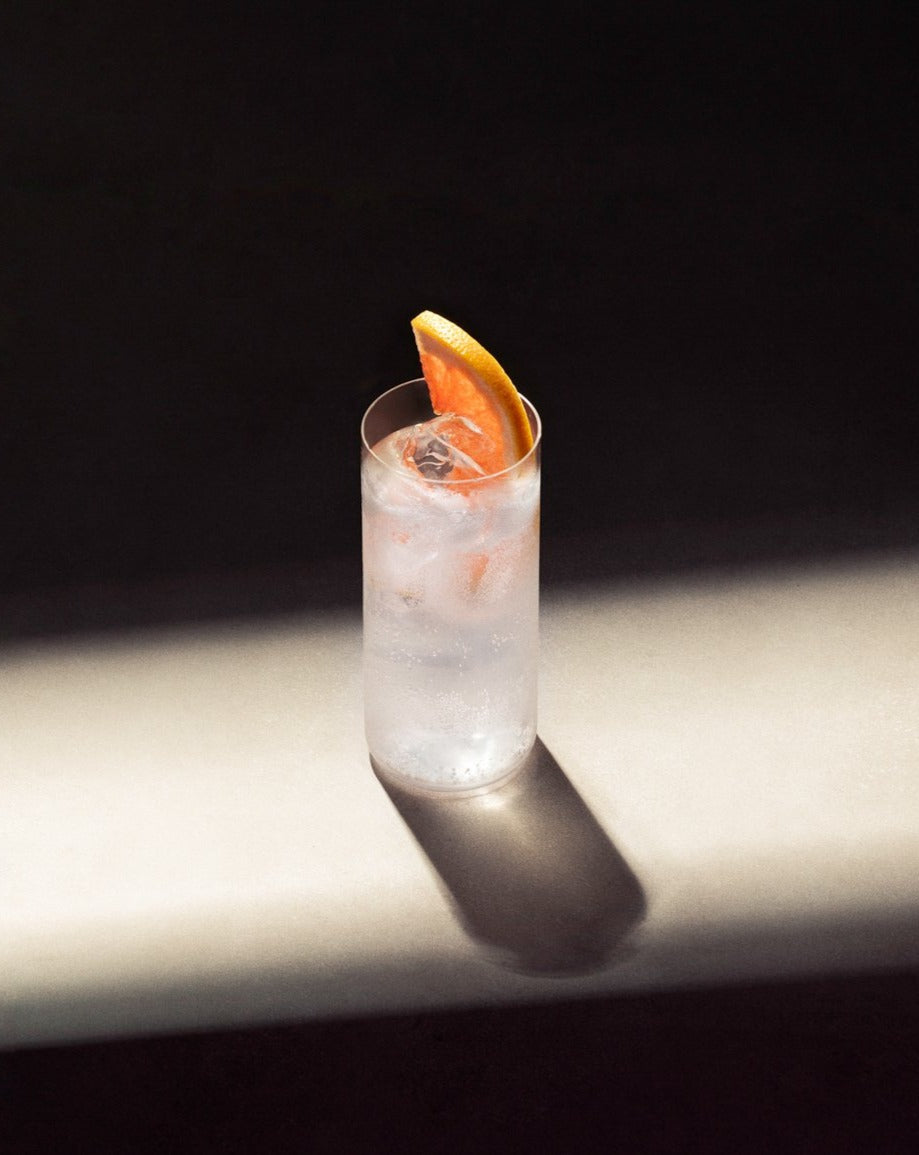 Paloma cocktail in a glass with ice and garnished with a slice of pink grapefruit.