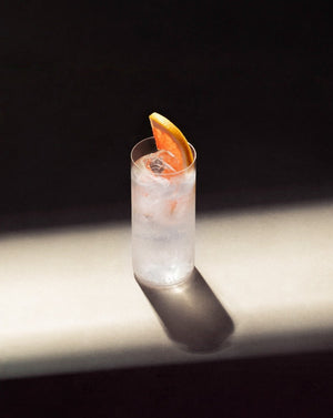Black Lines Paloma Cocktail in a clear highball glass with cubed ice garnished with a pink grapefruit slice.