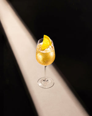 Black Lines Pear & White Tea Fizz Cocktail in a clear wine glass with cubed ice garnished with a lemon slice.