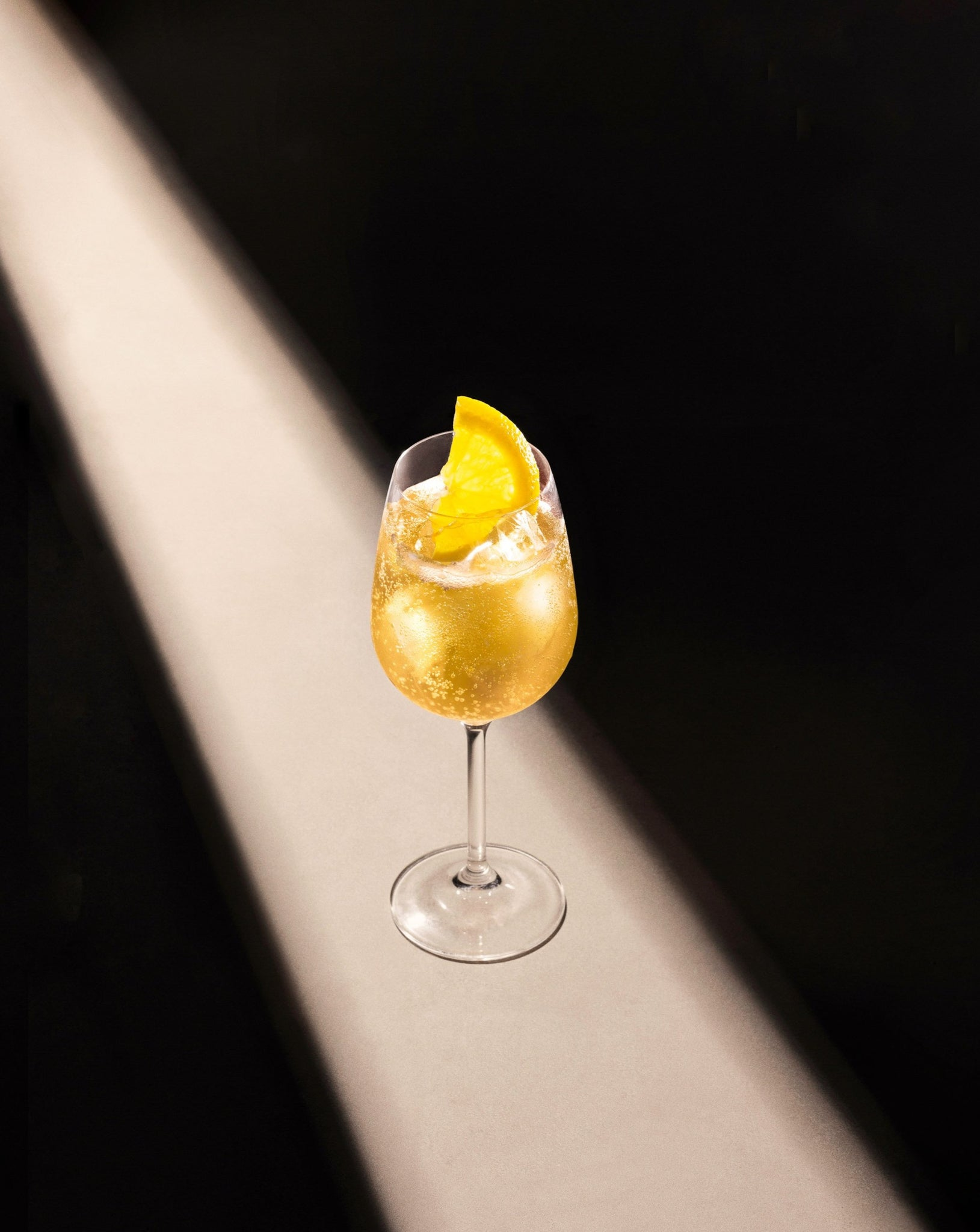Pear & White Tea Fizz cocktail in a wine glass garnished with a lemon slice.