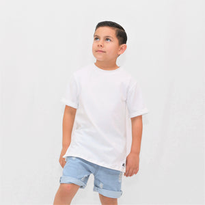 Onederful Co boy in white t-shirt and destructed denim shorts.