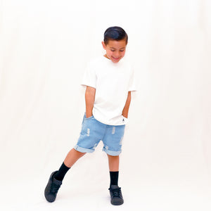Onederful Co. Boy in White T-Shirt and Destructed denim shorts.