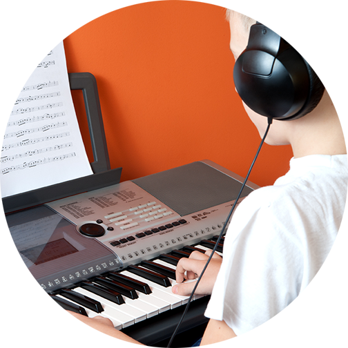 Child playing keyboard with headphones