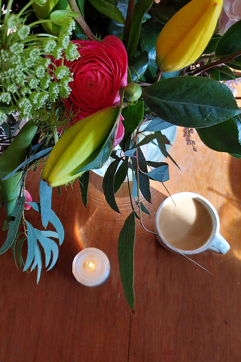 Spring bouquet with candle and coffee on wood table